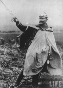 Kaiser_Wilhelm_II_standing_in_field_&_drawing_sword